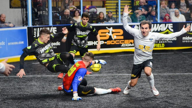 Wave goalkeeper Josh Lemos and defender Stuart Grable tangle at the ball while Cedar Rapids midfielder Antonio Aguilar begs for a penalty call.