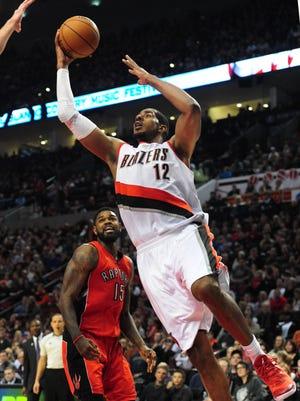 LaMarcus Aldridge drives to the basket on Toronto Raptors forward Amir Johnson.