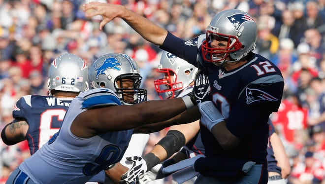 Tom Brady of the New England Patriots, right, is hit during the first quarter against the Detroit Lions on Nov. 23, 2014, in Foxboro, Mass.