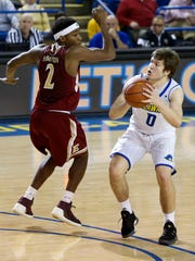 Delaware guard Ryan Daly shoots the tying basket in front of Elon's Dmitri Thompson in the second half of Delaware's 76-74 OT win at the Carpenter Center. His shot with 2 seconds left sent the game to overtime at 59-59.