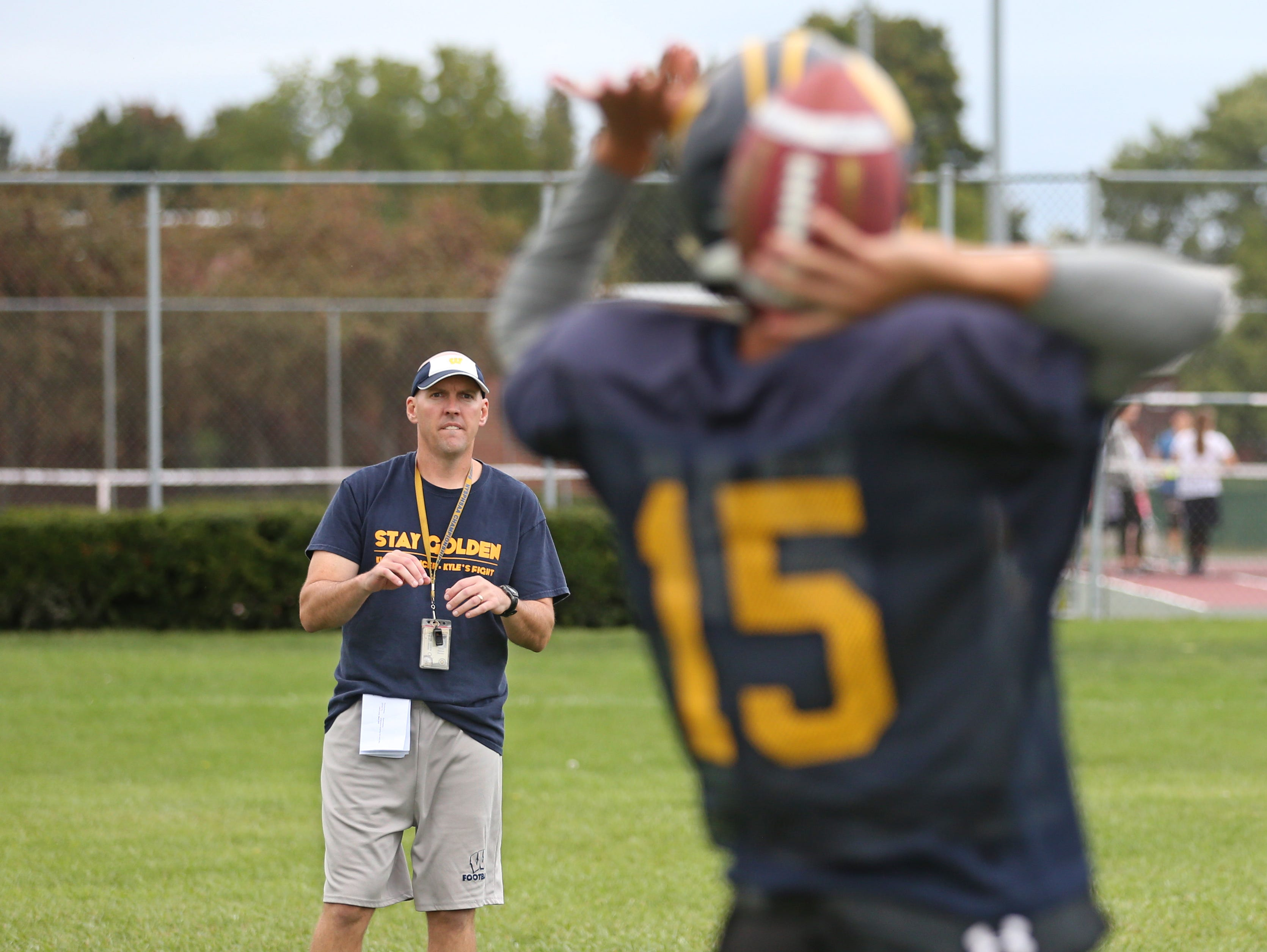 Wayne varsity football head coach David Marean warms up with his quarterback Braeden Zenelovic, during the team's practice at Wayne Central School in Ontario Monday, Sept. 28, 2015.