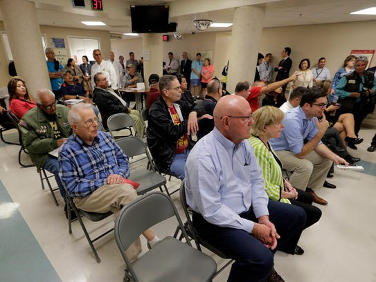 A roomful of veterans and administrators listen to