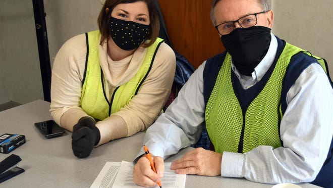 Voluteers Courtney Dirschell and Coldwater Township Supervisor Don Rogers check paperwork for those receiving COVID-19 vacinations Thursday at the Dearth Center.