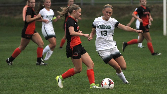 Ashland's Mackensi Meeting tries to take the ball from Madison's Taylor Huff during a match at Madison on Sept. 14.
