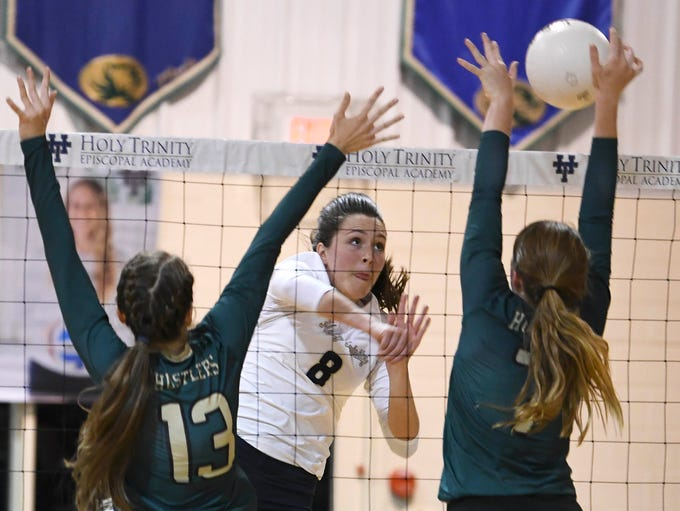 Holy Trinity's Emily Vaught spikes the ball over Claire