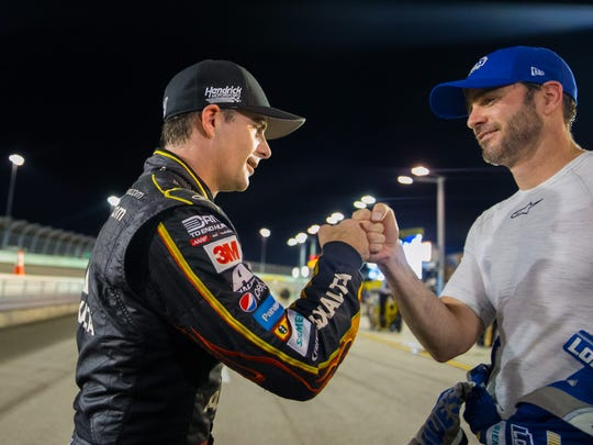 NASCAR Sprint Cup Series driver Jeff Gordon (left) fist bumps teammate Jimmie Johnson following qualifying for the Ford Ecoboost 400 at Homestead-Miami Speedway.
