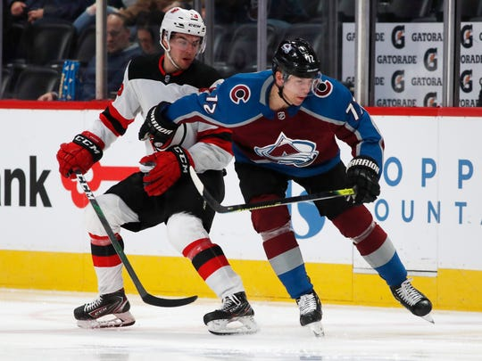 Colorado Avalanche right wing Joonas Donskoi, right, checks New Jersey Devils center Nico Hischier away from the puck in the second period of an NHL hockey game Friday, Dec. 13, 2019, in Denver. (AP Photo/David Zalubowski)