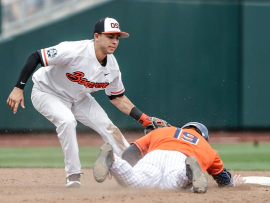 Oregon State second baseman Nick Madrigal, left, tags out Cal State Fullerton's Dillon Persinger (19) who was caught stealing second base in the third inning of an NCAA mens College World Series baseball game in Omaha, Neb., Saturday, June 17, 2017.