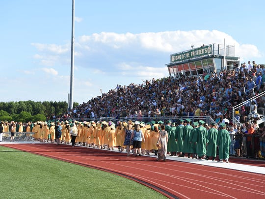 Graduating seniors pass the stands filled with family and friends during Franklin D. Roosevelt High School's 2016 graduation ceremony.