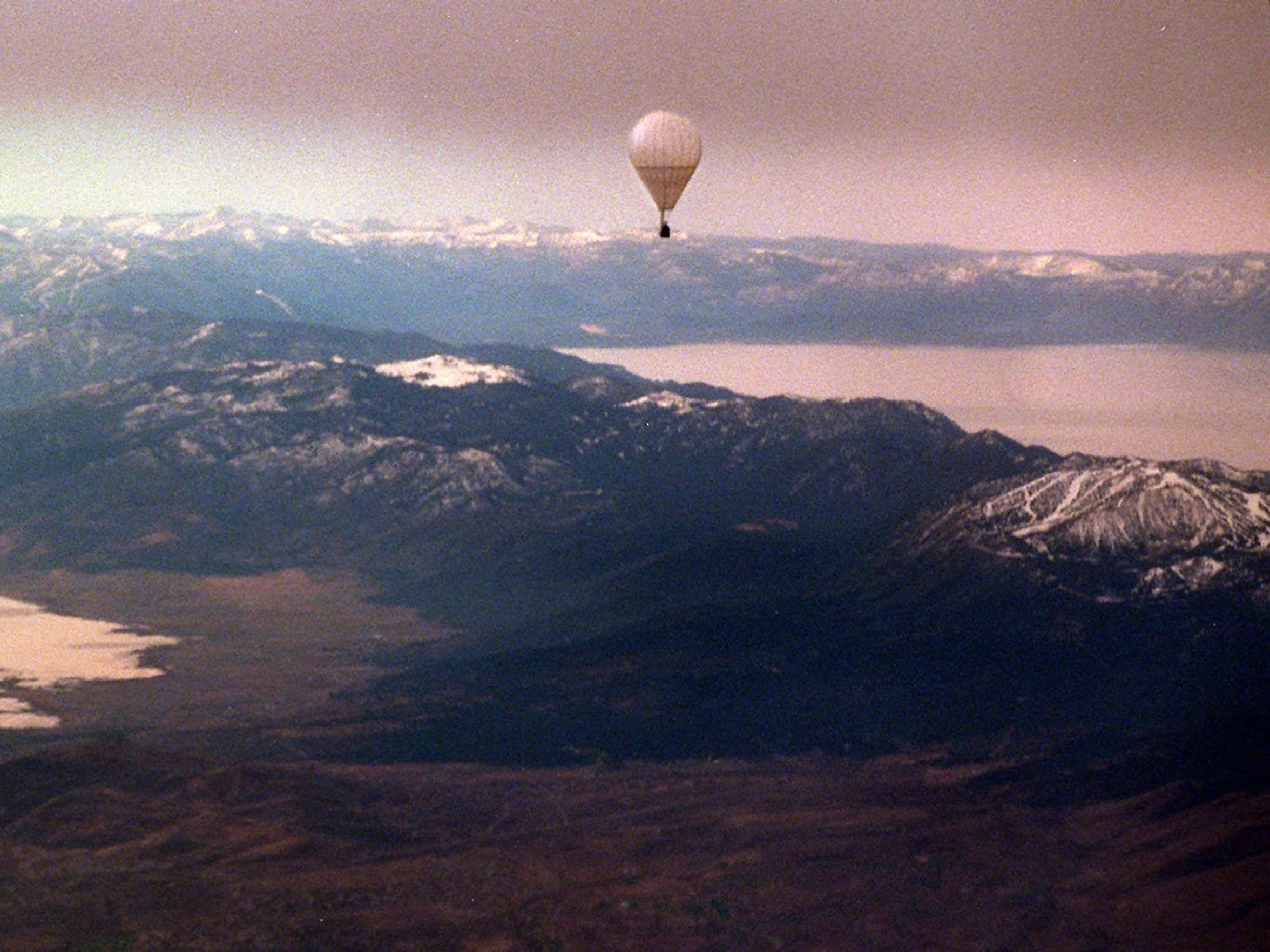 Lake Tahoe Balloons patrons embark on a skyward journey from an aquatic launch pad at sunrise.