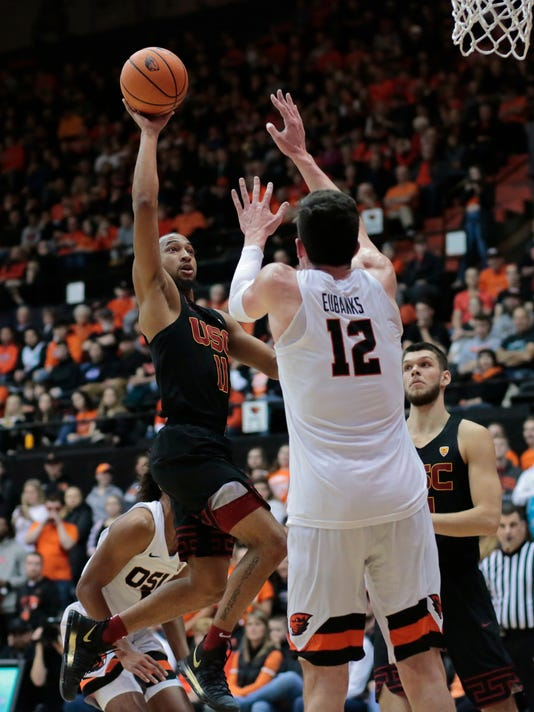 Southern California's Jordan McLaughlin (11) shoots over Oregon State's Drew Eubanks (12) in the first half of an NCAA college basketball game in Corvallis, Ore., Saturday, Jan. 20, 2018. (AP Photo/Timothy J. Gonzalez)