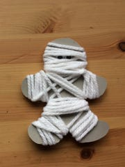Cardboard gingerbread men covered in white yarn look