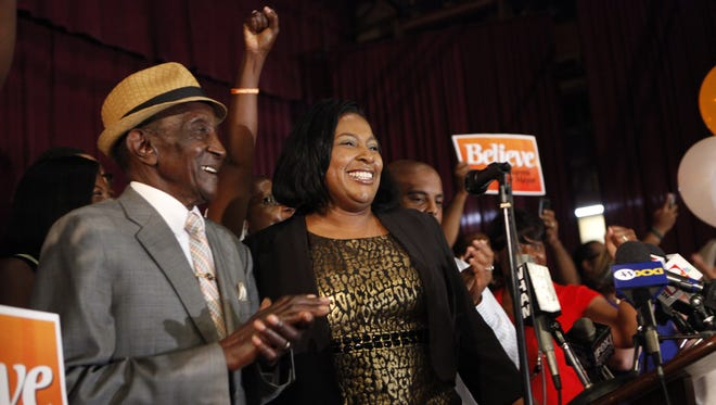 Lovely Warren celebrates her victory over Mayor Thomas Richards in the Democratic primary on Tuesday, Sept. 10, 2013. She is  accompanied by her grandfather, Cecil McClary, left.