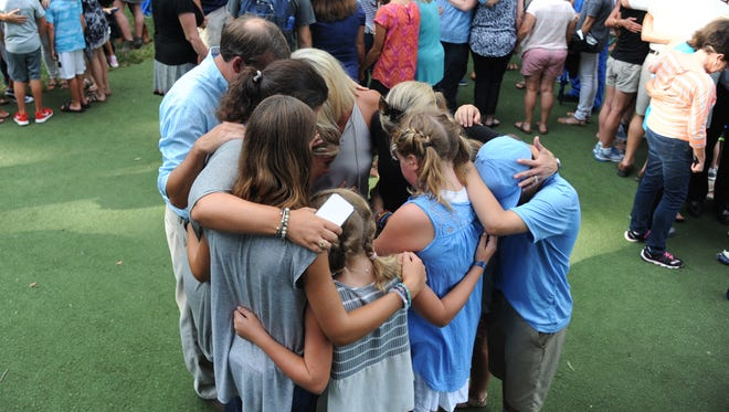 Mourners gather for a prayer vigil in Oxford, Miss. on Monday, August 15, 2016, for six people killed in a plane crash in Tuscaloosa, Ala. on Sunday. Three married couples killed in the crash of a small airplane in Alabama all lived in the university town of Oxford, Mississippi, where city flags were lowered Monday as residents grappled with the loss of so many lives at one time.