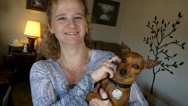 Tracy Straub, 45, with her miniature pinscher named Whino in her Trenton home.