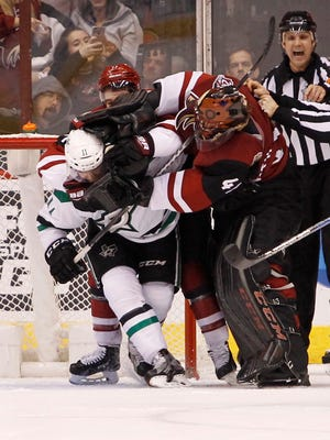 Coyotes goalie Mike Smith (41) and defenseman Anthony DeAngelo (77) tangle with Stars' Curtis McKenzie (11) after a play in front of the net during the second period, Tuesday, Dec. 27, 2016, in Glendale, Ariz.