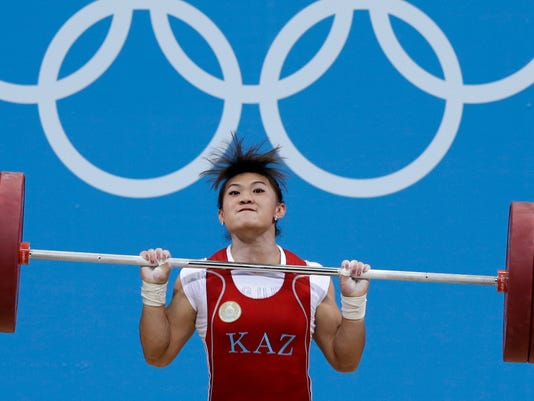 FILE - A Tuesday, July 31, 2012, photo from files of Maiya Maneza of Kazakhstan competing during the women's 63-kg, group A, weightlifting competition at the 2012 Summer Olympics, in London. Three female weightlifters from Kazakhstan, Maiya Maneza, Zulfiya Chinshanlo and Svetlana Podobedova have been stripped of gold medals from the 2012 London Olympics, Thursday Oct. 27, 2016, after failing retests of their doping samples.  (AP Photo/Hassan Ammar, File)