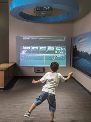 """A visitor enjoys an interactive tennis exhibit at The Franklin Institute's """"Your Brain."""""""