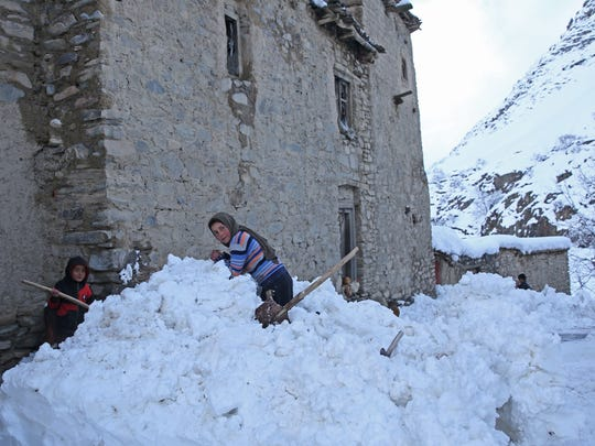 Afghan children look on in a village close to an avalanche