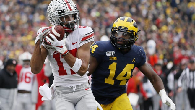 Ohio State wide receiver Chris Olave catches a touchdown pass behind Michigan defensive back Josh Metellus during the first quarter of last season's game, which Ohio State won handily, 56-27.