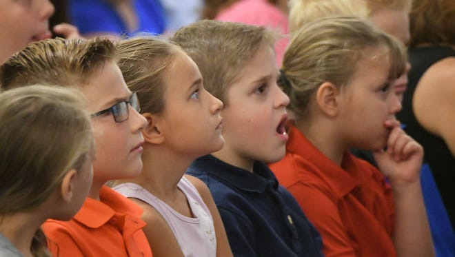 Temple Christian School students watch in awe while viewing a video montage showing the terrorist attacks of Sept. 11, 2001, Friday during a memorial ceremony.