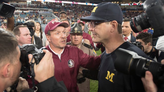 Florida State head coach Jimbo Fisher and Michigan head coach Jim Harbaugh shake hands after the game.