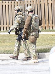 Officers dressed in tactical gear leave the scene of