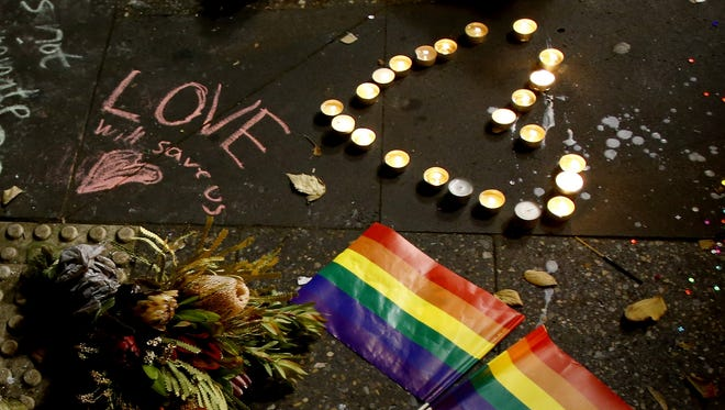 A man touches the ground next to rainbow flags during a candlelight vigil for the victims of the Pulse Nightclub shooting in Orlando, Florida, at Newtown Neighbourhood Centre on June 13, 2016 in Sydney, Australia.