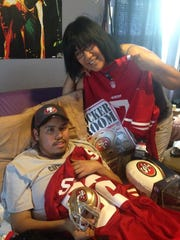 Alex Fernandez and his mother, Socorro Fernandez, display gifts from the San Francisco 49ers. At only 20 years old, he died from cancer. Going to a 49er game was on his bucket list.