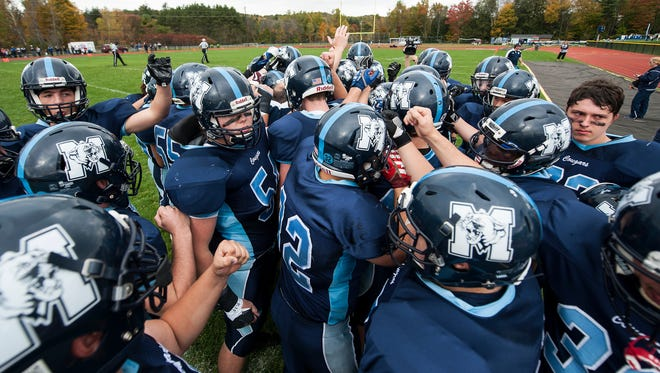 MMU huddles together before the start of the high school football game between the Hartford Hurricanes and the Mount Mansfield Cougars at MMU High School on Saturday afternoon October 14, 2017 in Jericho.
