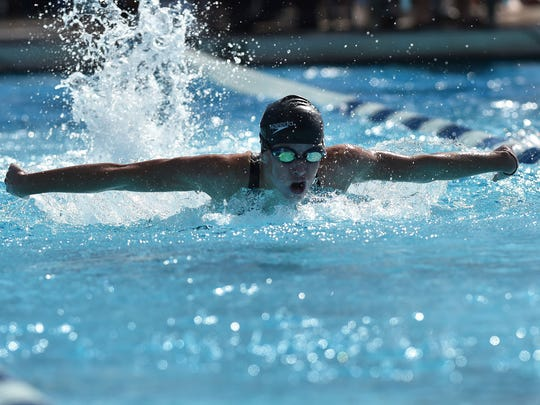 Madeline Burt, of St. John Newmann, competes in the first heat of the girls 100-yard butterfly during the preliminaries of the Florida High School Athletic Association Class 1A Swimming and Diving Finals on Friday, Nov. 11, 2016, at Sailfish Splash Waterpark in Stuart.