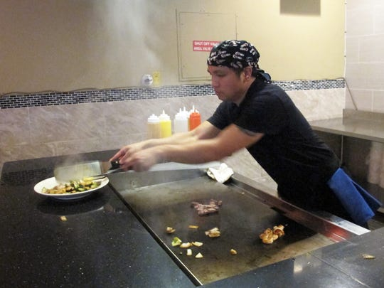 Yen Yang grills a hibachi steak and shrimp entree at