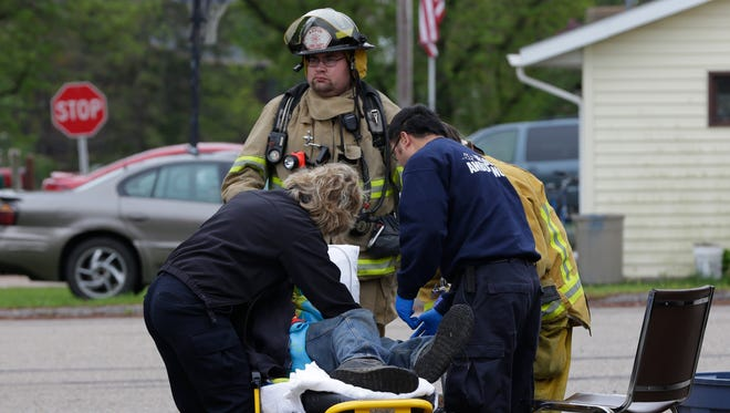 Firefighters and first responders from four departments attend to Robert Tritz after a house fire at 5228 3rd Ave in Pittsville, on Wednesday, May 11, 2016. Tritz has been transported to Madison for facial burns and smoke-inhalation injuries. A dog died in the blaze.