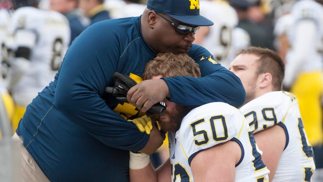 Michigan defensive end Tom Strobel, bottom, gets a hug from former player Will Carr on the sideline late in the loss to Ohio State on Saturday.