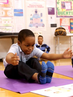 Davon Ethridge, 8, a third-grader at the Charles H. Wright Academy of Arts and Sciences in Detroit, works hard as he tries to reach for his toes during a Work It Out yoga class in the school gymnasium last week.