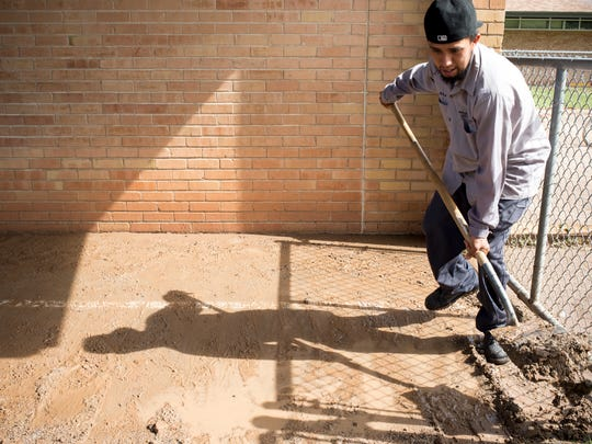 Santos Avila cleans up after last night's storms which caused damage to Sunland Elementary School in Phoenix. The storms damaged at least five schools in the Roosevelt Elementary School District, causing administrators to delay or alter class schedules