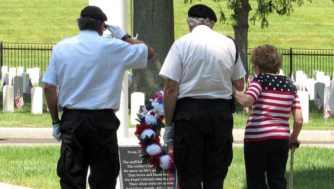 Therese Forte, right, widow of World War II and Korean War veteran Joseph Forte, takes part in  laying of the wreath Monday during a Memorial Day ceremony at Woodlawn National Cemetery in Elmira.
