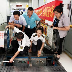 Staff members at an appliance store watch as officials from the local bureau of Quality and Technical Supervision inspect an escalator in Yongchuan district in southwest China's Chongqing Municipality Thursday July 30, 2015.