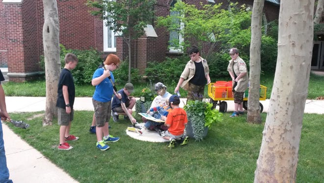 The scouts clean up a statue of a woman reading to a child.
