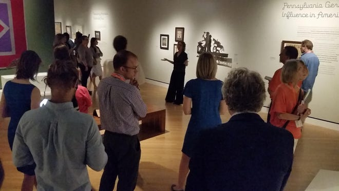"""A crowd listens to Stacy Hollander, center, curator of the American Folk Art Museum, speak about items in """"American Made: Treasures from the American Folk Art Museum"""" at the Crystal Bridges Museum of American Art in Bentonville. An exhibit of material from everyday craftsmen is on display through mid-September."""