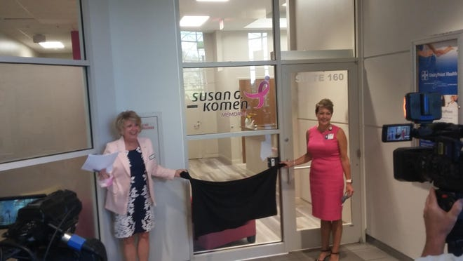 Gayle Young, left, mission director at the Susan G. Komen Memorial Affiliate, and Jeanette Murray, vice president of hospital operations at UnityPoint Health-Peoria, unveil the sign for the new Komen offices at the UnityPoint Atrium on Wednesday, Aug. 12, 2020.