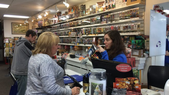 A worker at Gnome Games in Ashwaubenon helps a customer during Small Business Saturday on Nov. 29, 2014.