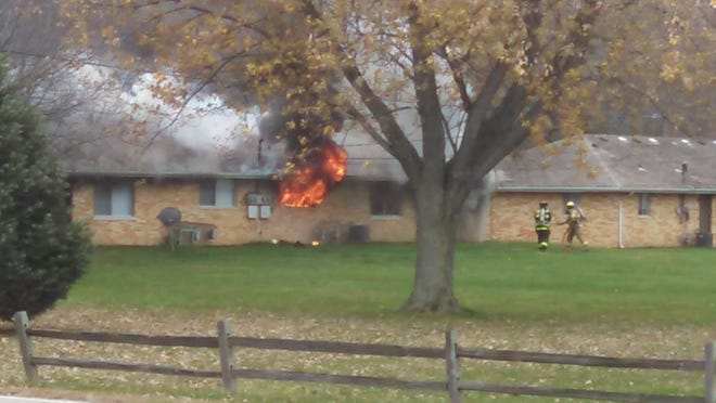 Fire and smoke erupt from a back window at Pemberly Court Apartments.