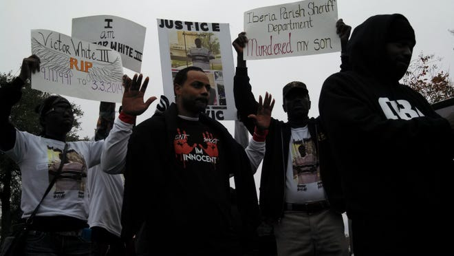 Victor White Sr. and other protesters display their signs for the police brutality march down Ambassador Caffery Parkway on Saturday afternoon.