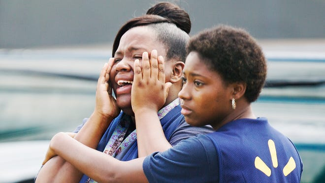 "Tyarra Hogan, left, and Diamond Black weep at the scene where Hogan's cousin, Lawerence Lockley, 17, was shot and killed Sunday in the Habitat Beecher Village neighborhood of Fort Myers. ""I don't know what I'm feeling,"" said Black. ""It just hurts."""