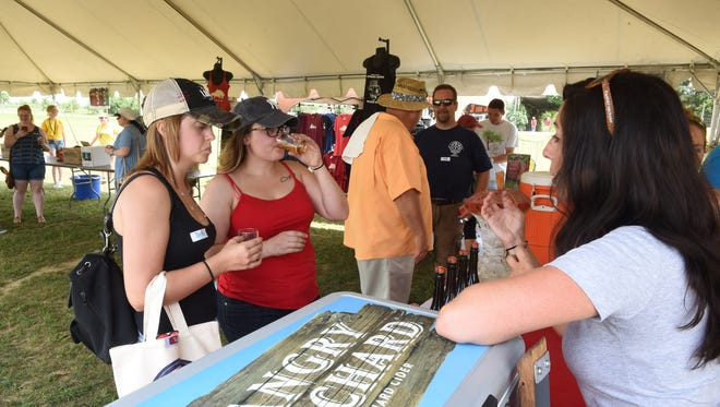 From left, Julia Spinner of of Stanfordville and Caitlynn Sherman of Poughkeepsie sample Angry Orchard Hard Cider from Jamie Corrao during the Hudson Valley Cider Festival at Barton Orchards in Poughquag on Saturday.