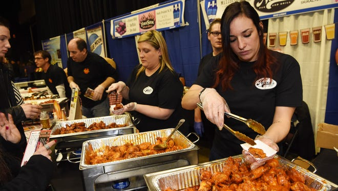 Noelle Willis, an employee at Nooch's Pub and Grill, serves up some wings at the 10th Annual Hudson Valley Wingfest at the Mid-Hudson Civic Center in the City of Poughkeepsie.