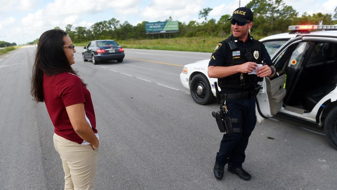 """Stephanie Stuart, a forensic psychology student at the Florida Institute of Technology and an intern with the Fellsmere Police Department, observes a traffic stop by Officer Jose Rendon on I-95 on June 28. As an intern with the department, Stuart will do ride-alongs with officers and accompany Police Chief Keith Touchberry to community events. """"Luckily, I don't have very much office work,"""" Stuart said."""