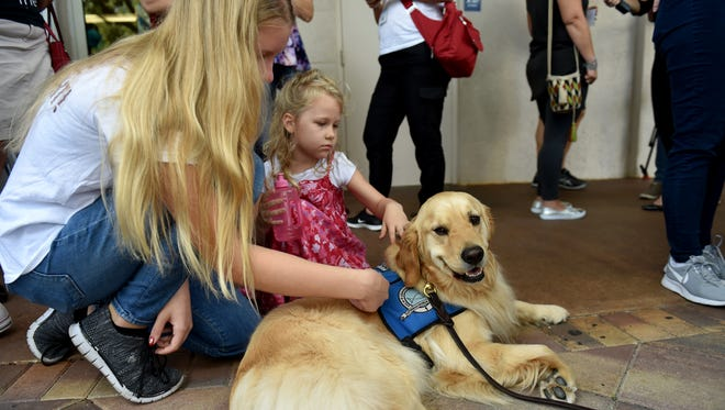 "Emmy Halulko, 13, (left) and her sister Evie, 5, both of Coral Springs stopped to pet Jacob, a Lutheran Church Charities comfort dog while at the Parkridge Church in Coral Springs Thursday, Feb. 15, 2018, for a community prayer vigil for all the shooting victims at Marjorie Stoneman Douglas High School. ""Awful"" Emmy said about the shooting before breaking down in tears, acknowledging she knew several people at the school."