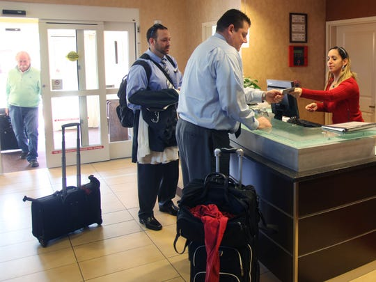 Jeff Whitcomb, left, and George Batalis, check in with Guest Services Manager Susana Castro at the Residence Inn Marriott on Thursday.
